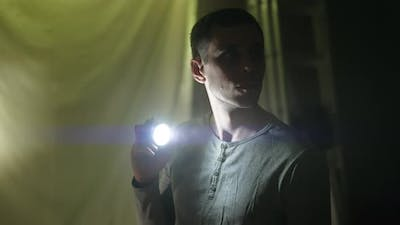 Man with a Flashlight Looking Around in a Dark Room