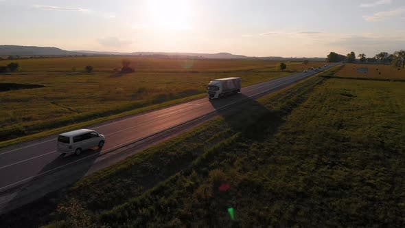 Aerial shot: vehicles, trucks and cars driving by road.