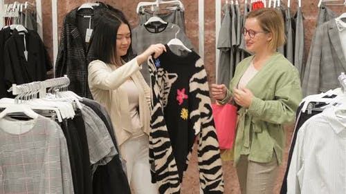 Beautiful girls are choosing clothes, talking and smiling