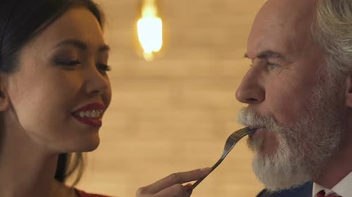 Young Woman Feeding Old Man, Flirting With Him, Love Despite Age Difference