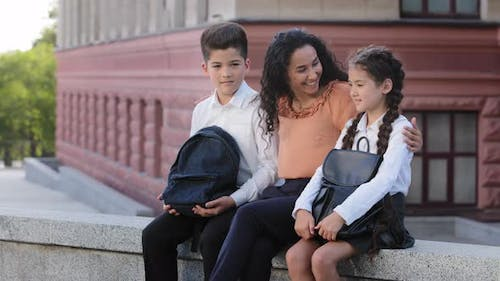 Young Woman Loving Mother Mom Teacher Sits in Schoolyard on Street Outdoors with Children Beloved