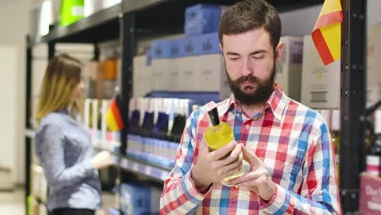 Thumbnail for Portrait of Young Handsome Caucasian Man Examining Label on Bottle of Expensive White Wine in Shop