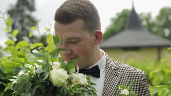 Thumbnail for Groom, Young Man in the Green Summer Park with a Wedding Bouquet. He Waiting for His Beloved Bride