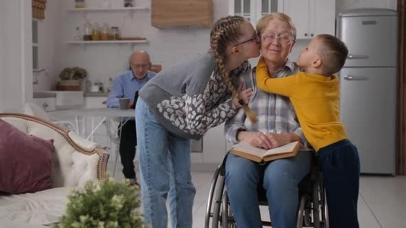 Loving Grandchildren Kissing Disabled Grandmother