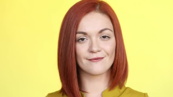 Thumbnail for Woman with Red Hair Smiling at Camera Over Yellow Background
