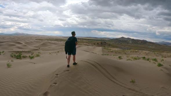 Following person walking on sand dunes through the Utah desert