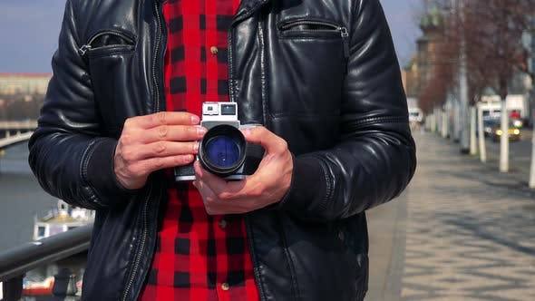 Thumbnail for A Man Holds a Camera Against His Chest in a Street - Closeup
