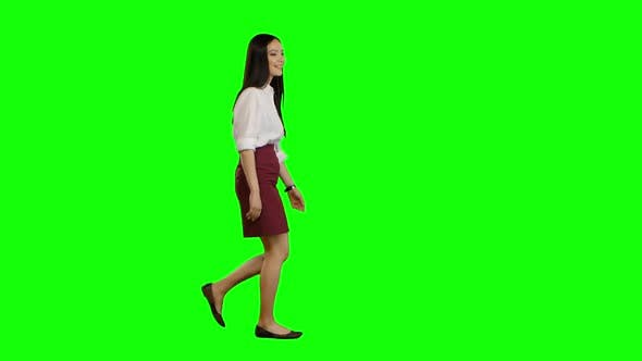 Thumbnail for Girl of Asian Appearance Goes To Work and Waves Her Hand. Green Screen. Side View