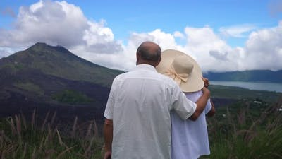 Back View of the Middleaged Couple Enjoying the View of an Island Landscape of Mountains and Ocean