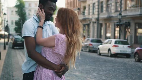Young Couple in Love Standing and Tenderly Cuddling on Streets of European Cities