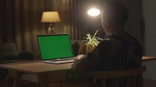 Teenager, der an seinem Schreibtisch sitzt und online auf einem Laptop mit grünem Mock-up-Bildschirm lernt