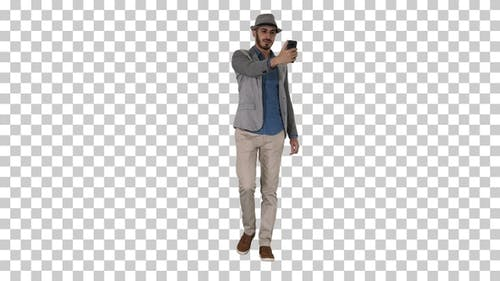 Arabian man in the casual clothes walking and making selfie