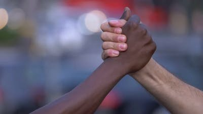 friendship, complicity, respect - black hand and white hand greet each other