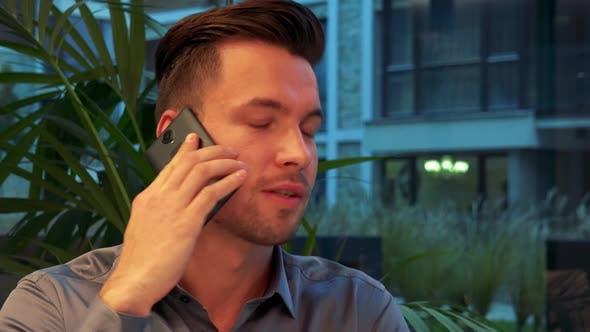 Thumbnail for Ein junger, gutaussehender Mann sitzt an einem Tisch in einem Restaurant und spricht auf einem Smartphone