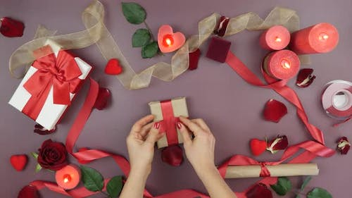 Female hands are tying red ribbon on gift box for St, Valentine's Day
