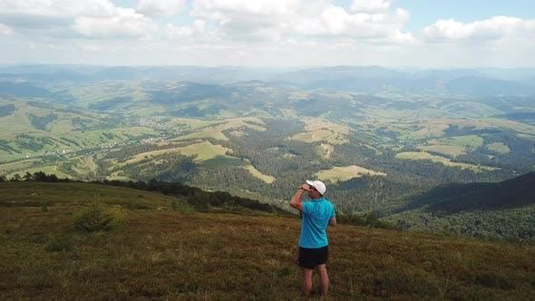 Young man tourist enjoys the mountain view.