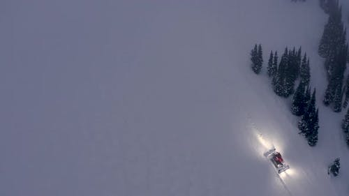 High Above Ski Slope View Of Snow Groomer Driving Over Snowfield To Improve Trail Conditions
