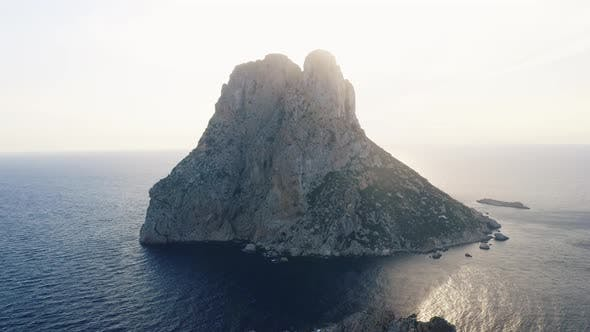 Towering Cliff in Ibiza Surrounded By Still Ocean Waters