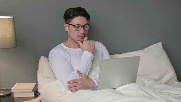 Pensive Middle Aged Man with Laptop Thinking in Bed