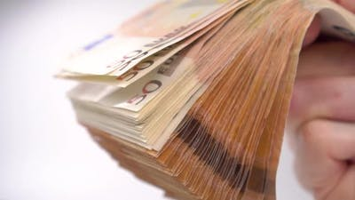 A wad of Euro money in hand close-up. Cash banknotes