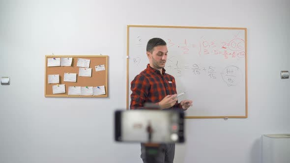 Young Math Teacher Ending His Online E-class with Waving Hand Looking at the Camera