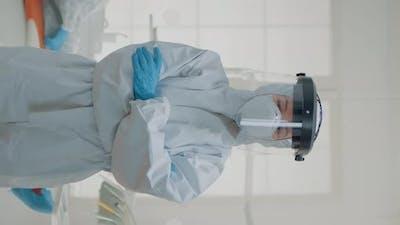 Vertical Video Portrait of Dentist Standing in Hazmat Suit for Virus Protection