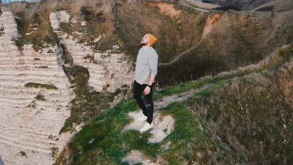 Thumbnail for Drone Flying Around Happy Young Travel Blogger Man Watching Breathtaking Sunset View on Top of Coast