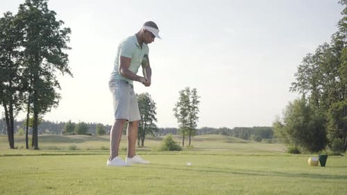 Portrait Handsome Beginner Middle Eastern Golfer Swinging and Hitting Golf Ball on Beautiful Course