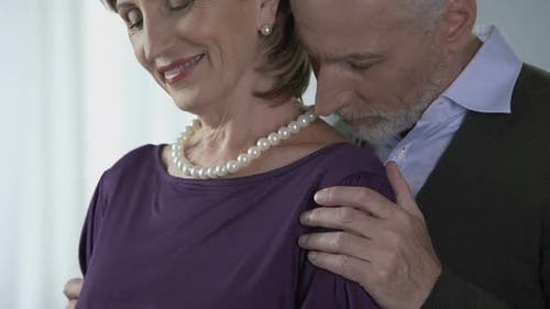 Elderly Male Kissing Female in Pearls on Shoulder, Special Occasion, Happiness