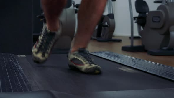 Thumbnail for A Fit Man Jogs on a Treadmill in a Gym - Front Closeup on the Feet
