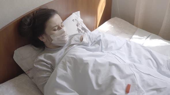 Sad Caucasian Brunette Woman Measuring Body Temperature with Thermometer. Unhappy Ill Caucasian Girl