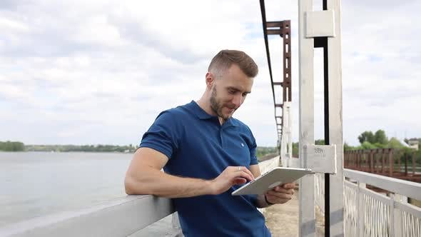 Thumbnail for A guy with a tablet in his hands is standing on the bridge