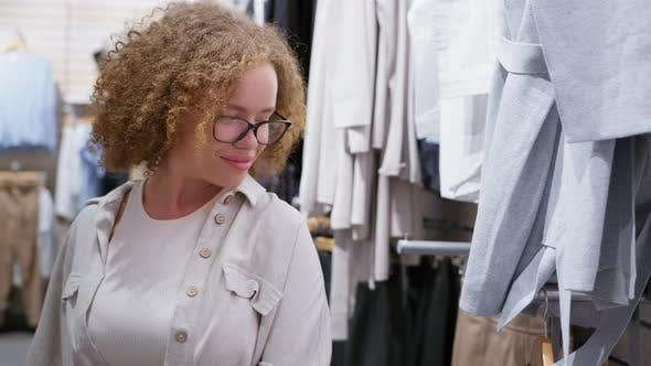 Female Customer Looks at Things on Shelves of Retail Store
