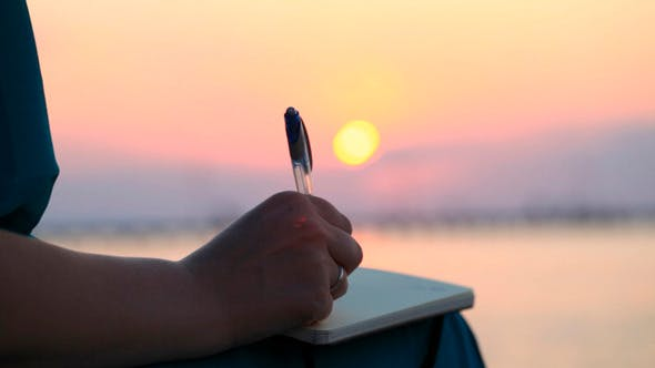 Thumbnail for Woman Writing in Her Diary at Sunset
