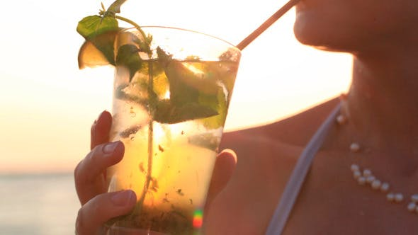 Cover Image for Woman Enjoying a Tropical Mojito Cocktail