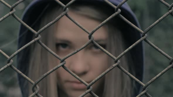 Thumbnail for Portrait of Moody and Sad Blonde Caucasian Girl Behind the Iron Fence. Young Woman Behind Metal