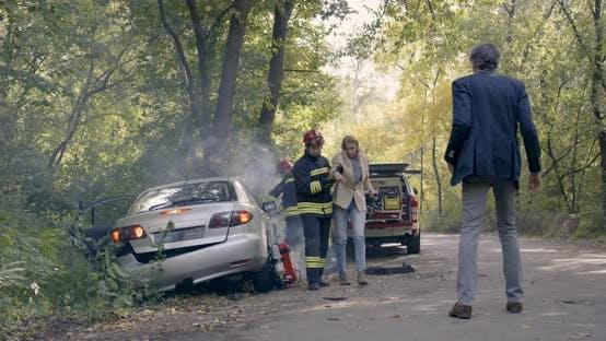 Firefighters Saving Woman From Car Near Mature Man