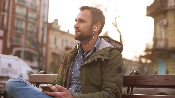 Handsome Man Listening Music in Earphones in City Park Sitting on Bench