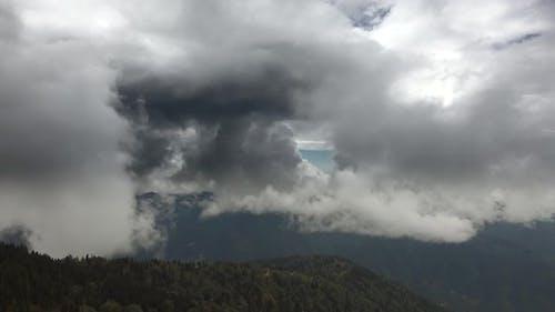 Dickschichtige Hochwolken in bewaldeten Bergen
