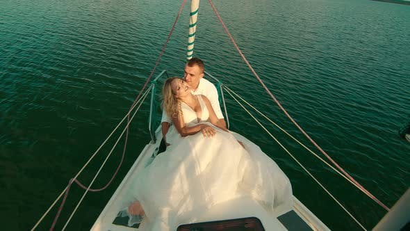 The Bride and Groom Are Sitting on a Yacht. Bride with Closed Eyes