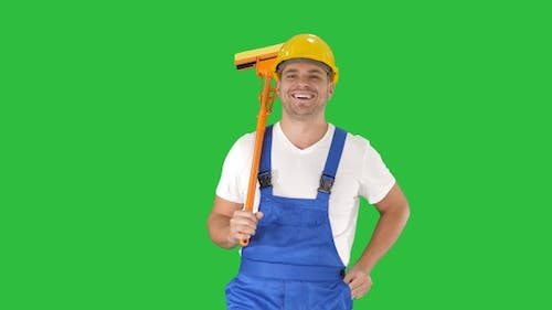 Housecleaner in helmet walking with a mop on a Green Screen