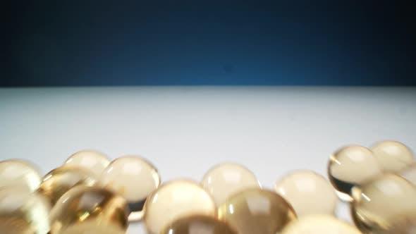 Spilling Gold Gel Balls On White Surface