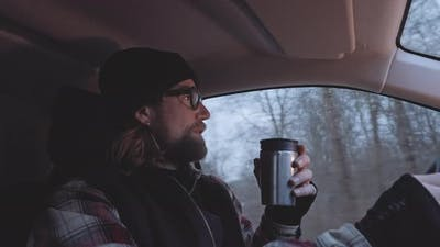 Bearded Man In Glasses Driving And Drinking Coffee