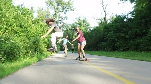 Three cool cheerful friends skateboarding