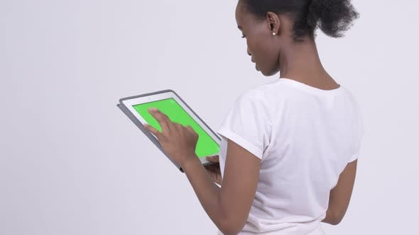 Thumbnail for Rear View of Young Beautiful African Woman Using Digital Tablet