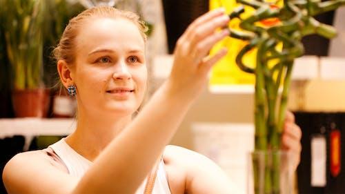 Beautiful Woman Arranging Ornamental Bamboo