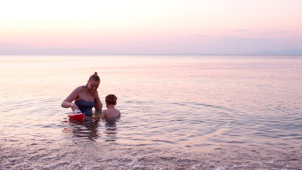 Thumbnail for Mother Playing With Young Son With Toy Boat