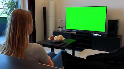 Woman Sits on Couch in Living Room, Watches TV Green Screen
