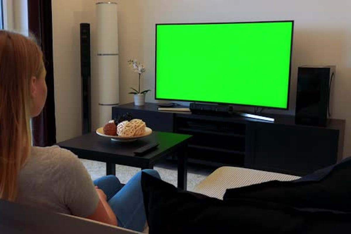 Woman Sits On Couch In Living Room Watches Tv Green Screen By Thopter24 On Envato Elements