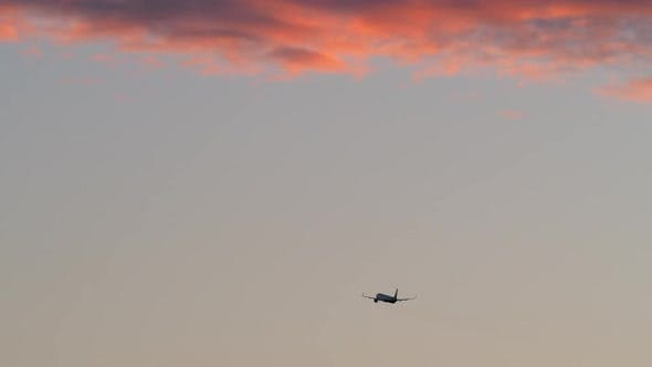 Thumbnail for - Airplane Flying in Evening Sky with Red Clouds